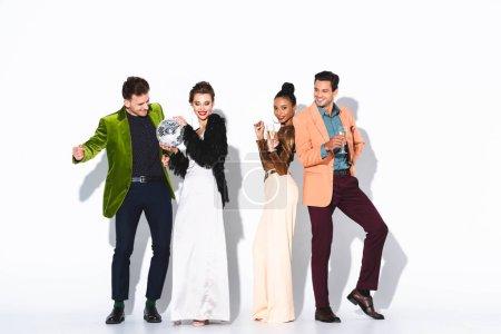 Photo pour Joyeux et chic amis multiculturels tenant des lunettes de champagne et un ballon de disco blanc - image libre de droit