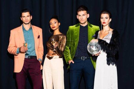 Photo pour Belles femmes multiculturelles et beaux hommes tenant des verres de champagne sur bleu foncé - image libre de droit