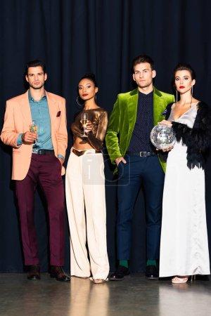 Photo pour Séduisantes femmes multiculturelles et beaux hommes tenant des verres à champagne sur bleu foncé - image libre de droit