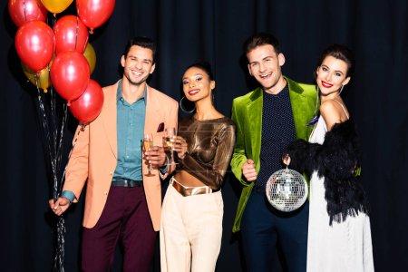Photo pour Heureuses femmes multiculturelles et beaux hommes tenant des verres de champagne près de ballons sur bleu foncé - image libre de droit