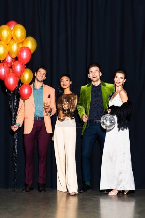 Photo pour Cheerful multicultural women and handsome men holding champagne glasses near balloons on dark blue - image libre de droit
