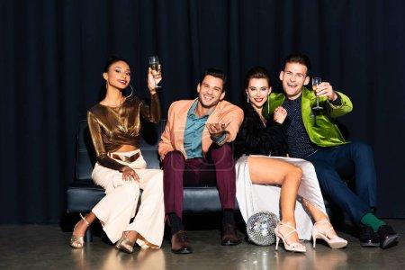 Photo pour Femmes multiculturelles gaies et beaux hommes tenant des verres de champagne assis sur le canapé sur bleu foncé - image libre de droit