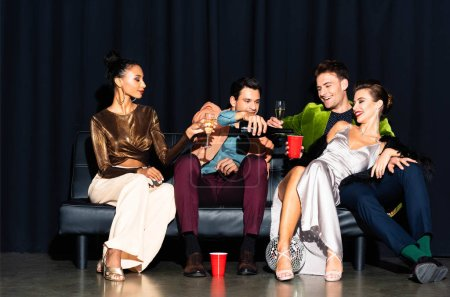 Photo pour Bel homme versant du champagne dans une tasse en plastique près d'une femme multiculturelle assise sur un canapé bleu foncé - image libre de droit