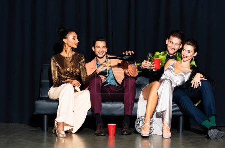 Photo pour Homme joyeux versant champagne dans une tasse en plastique près de femme multiculturelle tout en étant assis sur le canapé sur bleu foncé - image libre de droit