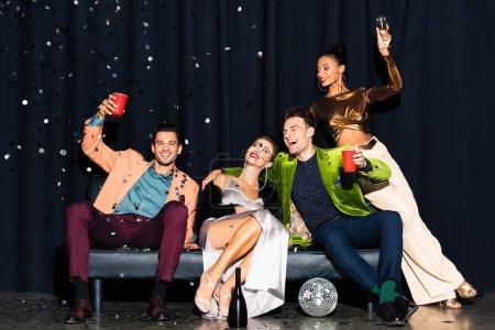 Photo pour Des amis multiculturels gaiement assis sur un canapé près de tomber confetti sur bleu foncé - image libre de droit