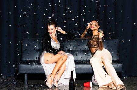 Photo pour Belles filles multiculturelles assis sur le canapé près de tomber confettis sur bleu foncé - image libre de droit