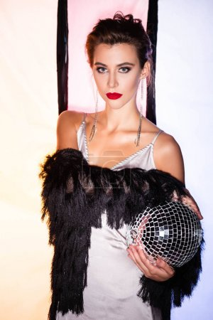 Photo pour Chic femme tenant une balle de disco brillante sur blanc avec des rayures noires - image libre de droit