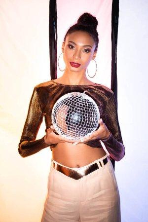 Photo pour Élégant afro-américain fille tenant brillant boule disco sur blanc avec des rayures noires - image libre de droit
