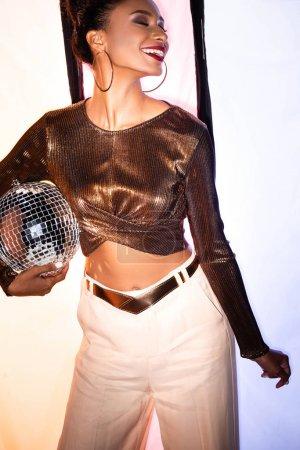 Photo pour Heureux afro-américain fille tenant brillant boule disco sur blanc avec des rayures noires - image libre de droit