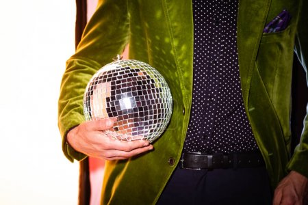 Photo for Cropped view of man holding shiny disco ball on white - Royalty Free Image