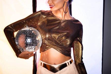 Photo pour Vue recadrée de heureuse fille afro-américaine tenant boule disco brillant sur blanc avec des rayures noires - image libre de droit