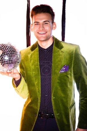 Photo pour Joyeux homme en blazer vert tenant une balle de disco brillante sur blanc avec des rayures noires - image libre de droit