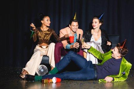 Photo pour Happy multicultural friends in party caps clinking near disco ball on dark blue - image libre de droit