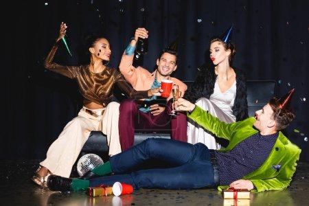 Photo pour Des amis multiculturels gaiement en coiffe de fête près de la boule de disco sur bleu foncé - image libre de droit