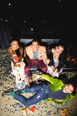 Photo pour Overhead view of cheerful multicultural friends holding drinks near disco ball - image libre de droit