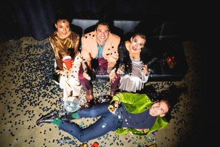 Photo pour Vue d'ensemble d'hommes et de femmes multiculturels joyeux prenant un verre près d'un bal de discothèque - image libre de droit
