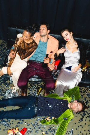Photo pour Overhead view of tired multicultural friends sleeping on sofa near disco ball - image libre de droit