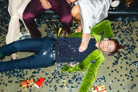 Photo for Handsome and drunk man sleeping on floor near friends and confetti after party - Royalty Free Image
