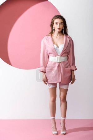 Photo pour Fille élégante debout et regardant la caméra sur blanc et rose - image libre de droit