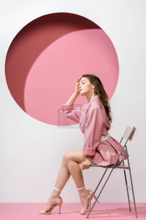beautiful girl sitting on chair on white and pink