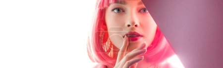 panoramic shot of attractive woman touching lips and looking at camera on white and pink