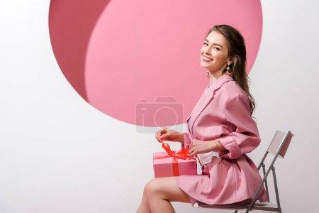 Photo pour Femme heureuse assise sur la chaise et tenant présent sur blanc et rose - image libre de droit