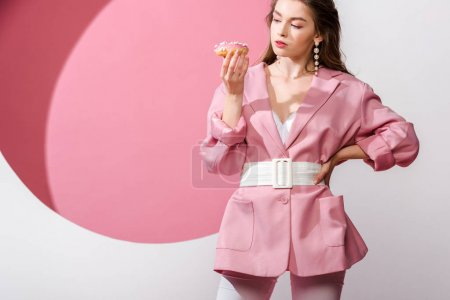 attractive woman standing with hand on hip and looking at sweet doughnut on white and pink