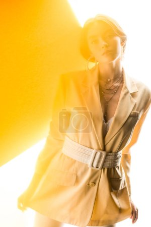 Photo for Attractive woman looking at camera on white and yellow - Royalty Free Image