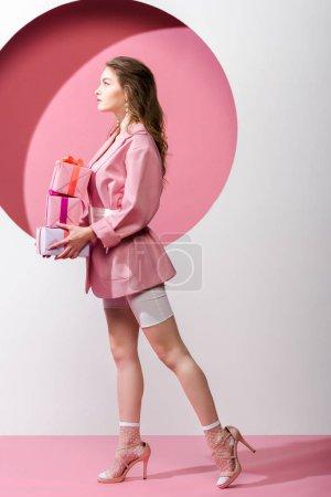 Photo pour Vue latérale de attrayant femme exploitation présente sur blanc et rose - image libre de droit