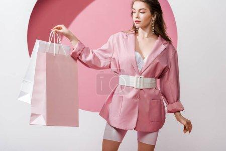 Foto de Hermosa chica mirando las bolsas de compras en blanco y rosa - Imagen libre de derechos