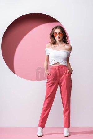 Foto de Chica atractiva en gafas de sol de pie con las manos en los bolsillos en rosa y blanco - Imagen libre de derechos