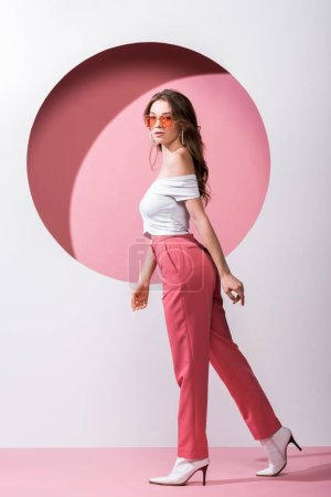Photo for Beautiful girl in sunglasses walking on white and pink - Royalty Free Image