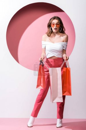 surprised girl in sunglasses holding shopping bags on white and pink