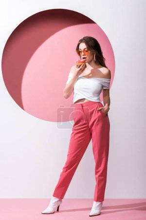 beautiful girl holding tasty doughnut and standing with hand in pocket on pink and white