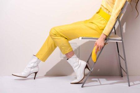 Foto de Vista cromada de la mujer sentada en la silla y que sostiene el plátano amarillo sobre blanco - Imagen libre de derechos