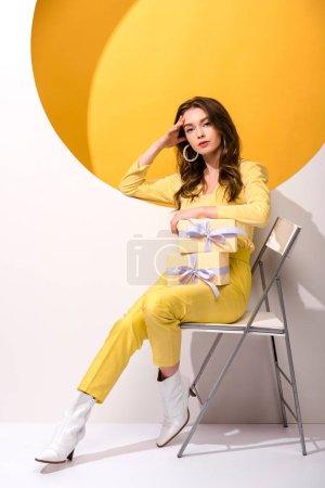 Photo pour Jolie femme assise sur une chaise et tenant des cadeaux sur orange et blanc - image libre de droit
