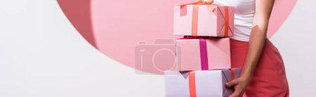 Photo pour Prise de vue panoramique de femme tenant des cadeaux tout en se tenant debout sur rose et blanc - image libre de droit