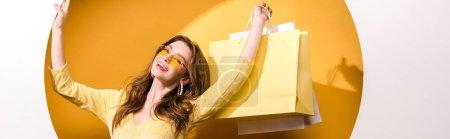 Photo pour Plan panoramique de femme heureuse dans des lunettes de soleil tenant des sacs à provisions sur orange et blanc - image libre de droit