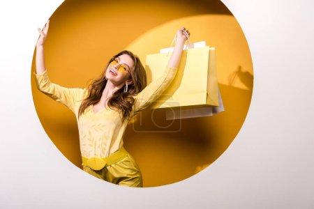 Photo pour Femme positive dans des lunettes de soleil tenant des sacs à provisions sur orange et blanc - image libre de droit