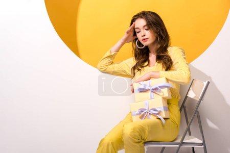 Photo pour Jolie femme regardant des cadeaux sur orange et blanc - image libre de droit