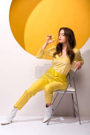 Photo pour Jolie femme assise sur une chaise et tenant des macarons sur orange et blanc - image libre de droit
