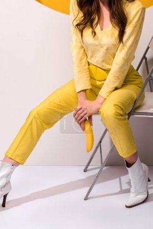 Photo for Cropped view  of woman sitting on chair and holding banana on white and orange - Royalty Free Image
