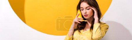 Foto de Foto panorámica de la mujer joven que tiene banano en blanco y naranja - Imagen libre de derechos