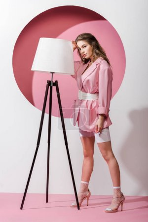 beautiful woman standing near floor lamp on white and pink