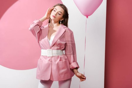 Photo pour Attractive young woman standing and holding balloon on pink and white - image libre de droit