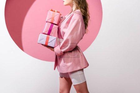 Photo pour Vue recadrée de femme tenant des cadeaux sur rose et blanc - image libre de droit