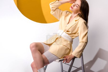 stylish young woman sitting on chair and touching hair on white and orange