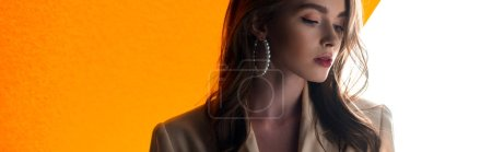 panoramic shot of young attractive woman on orange and white