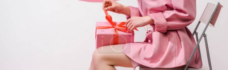Photo pour Plan panoramique de fille touchant arc sur cadeau sur blanc - image libre de droit