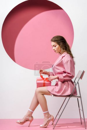 Photo for Attractive girl touching bow on gift while sitting on white and pink - Royalty Free Image